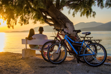 Pic 1 Couple relaxing on beach with bikes 2018